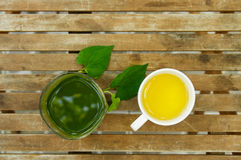A green juice glass & a tea cup on wooden table in the garden. In daylight royalty free stock photography