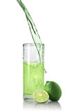 Green juice with lime pouring into glass. Isolated on white royalty free stock photo
