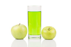 Green juice standing between two green apples with water drops on surface on white background. Royalty Free Stock Photography