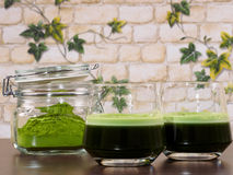Green juice. Two glasses of green juice, one full and a jar of green juice powder, set over a wenge board, with a background of brick wall and ivy leafs Stock Images