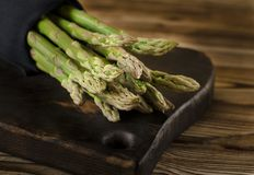 Green juicy asparagus is lying on a wooden board on a brown wooden table stock photos