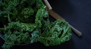 Green Kale and knife on black background on daylight superfood Still life. Green Kale and knife on black background top view on daylight superfood vegetables stock photos