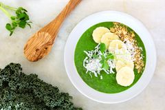 Green kale smoothie bowl overhead scene on white marble. Green smoothie bowl with kale, bananas, granola, pea shoots and coconut. Overhead scene on white marble Stock Photography