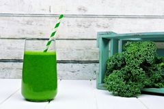 Green kale smoothie in a glass with crate of kale Royalty Free Stock Images