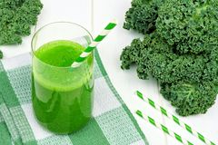 Green kale smoothie with straws on checkered cloth. Green kale smoothie in a glass with straws on a checkered cloth against white wood Royalty Free Stock Photo