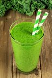 Green kale smoothie on wood background. Green kale smoothie in a glass with straws on a rustic wood background Stock Photos