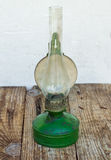 Green kerosene lamp. Old green kerosene lamp on the wooden table Stock Photos