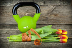 Green kettlebells and tied with a measuring tape bouquet of tulips flowers on a wooden background. Stock Photos