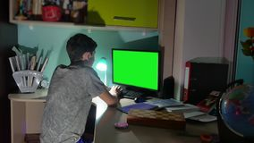 Green key indoors teenage boy playing computer close-up hands game video sitting back. Young student examinations man. Working on computer at home at night stock video footage
