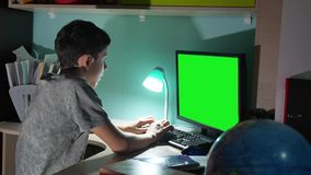 Green key indoors teenage boy playing computer close-up hands game video sitting back. Young student examinations man. Working on computer at home at night in stock video