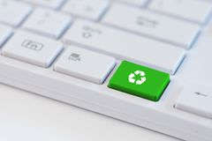 A green key with recycle icon symbol on white laptop keyboard. Recycling concept: A green key with recycle icon symbol on white laptop keyboard Stock Photo