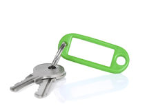 Green keyring. Two keys on a blank keyring with space for text, isolated on white Royalty Free Stock Image