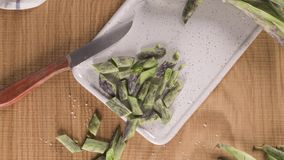 Green kidney bean. On brown wooden cutting board with kitchen knife stock video footage