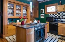 Green Kitchen with China Cabinet. Dayton, Ohio, USA - June 18, 2018: Green kitchen with built-in china cabinet, center island, black & white themed decor & back royalty free stock images