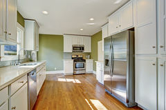 Green kitchen room with white storage combination. Steel stainless appliances and hardwood floor stock photos
