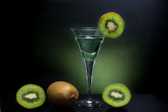 Green kiwi drink, cold and clear drink in high glass with whole. Kiwi in background Royalty Free Stock Photo