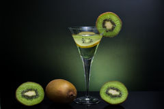 Green kiwi drink, cold and clear drink in high glass with whole. Kiwi in background Stock Image
