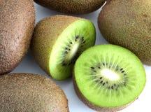 Green Kiwi fruit cut in half next to whole one isolated on white. Green Kiwi cut in half next to whole one isolated on white background royalty free stock photo