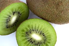 Green Kiwi fruit cut in half next to whole one isolated on white background stock photo