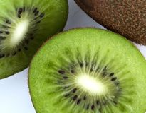 Green Kiwi fruit cut in half next to whole one on white background. Green Kiwi cut in half next to whole one on white background royalty free stock images