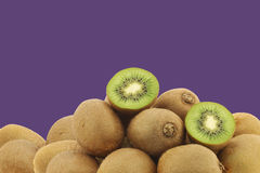 Green kiwi fruit and a cut one Stock Photos
