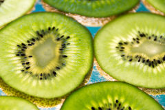 Green kiwi fruit slices on lighted glass. Photograph of some green kiwi fruit slices on lighted glass Stock Image