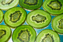 Green kiwi fruit slices on lighted glass. Photograph of some green kiwi fruit slices on lighted glass Royalty Free Stock Photo