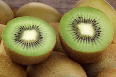 Green kiwi fruit and some cut ones. Against a wooden box background Royalty Free Stock Photo