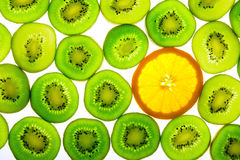 Green kiwi with one orange slice Stock Image