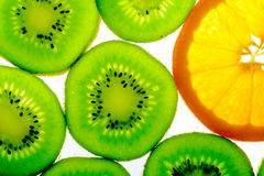 Green kiwi with one orange slice Royalty Free Stock Images
