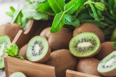 Green kiwis and mint leaves in the wooden tray. Soft focus background royalty free stock image
