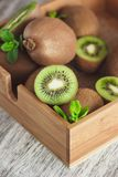 Green kiwis and mint leaves in the wooden tray. Soft focus background royalty free stock photography