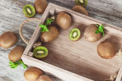 Green kiwis and mint leaves in the wooden tray. Soft focus background stock photography