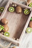 Green kiwis and mint leaves in the wooden tray. Soft focus background royalty free stock photo