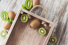 Green kiwis and mint leaves in the wooden tray. Top view stock photo