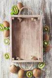 Green kiwis and mint leaves in the wooden tray. Top view stock photography