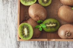 Green kiwis and mint leaves in the wooden tray. Top view stock images