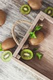 Green kiwis and mint leaves in the wooden tray. Top view stock photos
