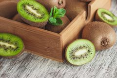 Green kiwis and mint leaves in the wooden tray. Soft focus background stock image