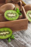 Green kiwis and mint leaves in the wooden tray. Soft focus background stock photo