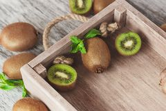 Green kiwis and mint leaves in the wooden tray. Soft focus background stock images