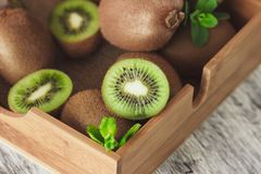Green kiwis and mint leaves in the wooden tray. Soft focus background stock photos