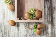 Green kiwis and mint leaves in the wooden tray. Top view royalty free stock photos