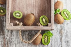 Green kiwis and mint leaves in the wooden tray. Top view royalty free stock images