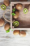 Green kiwis and mint leaves in the wooden tray. Top view royalty free stock photography