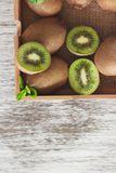 Green kiwis and mint leaves in the wooden tray. Top view royalty free stock photo