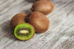 Green kiwis on the wooden background. Soft focus background stock images