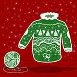 Green knitted christmas sweater and a ball of yarn. On red background Stock Image