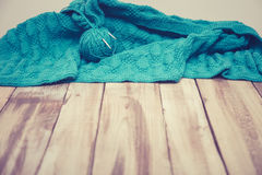 Green knitted cloth laying on wooden table Stock Photography