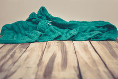 Green knitted cloth laying on wooden table Royalty Free Stock Photos